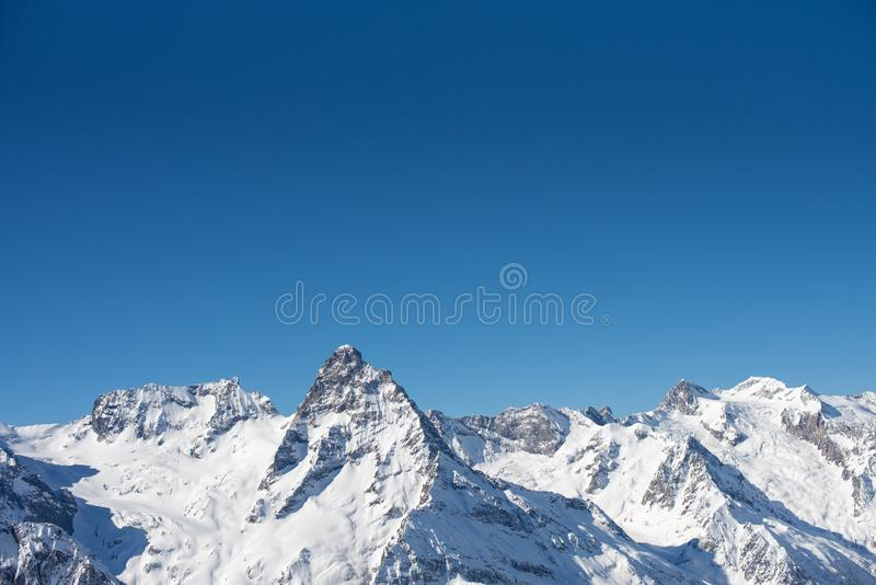 Winter mountains with snow and blue sky in nice sun day. Ski resort and sport concept. Caucasus Mountains, region Dombay. View. From the top of Musa Achitara stock images