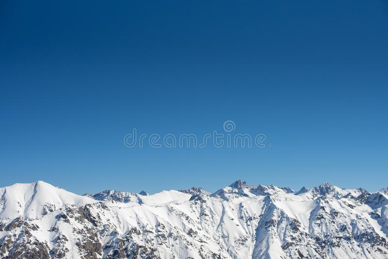 Winter mountains with snow and blue sky in nice sun day. Ski resort and sport concept. Caucasus Mountains, region Dombay. View from the top of Musa Achitara stock image