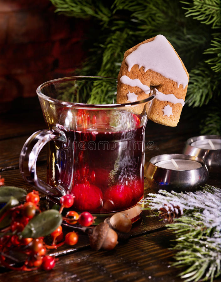 Winter mug hot red drink with cookie . Winter hot drink. Warming mulled wine with cookie in form of house stock photography