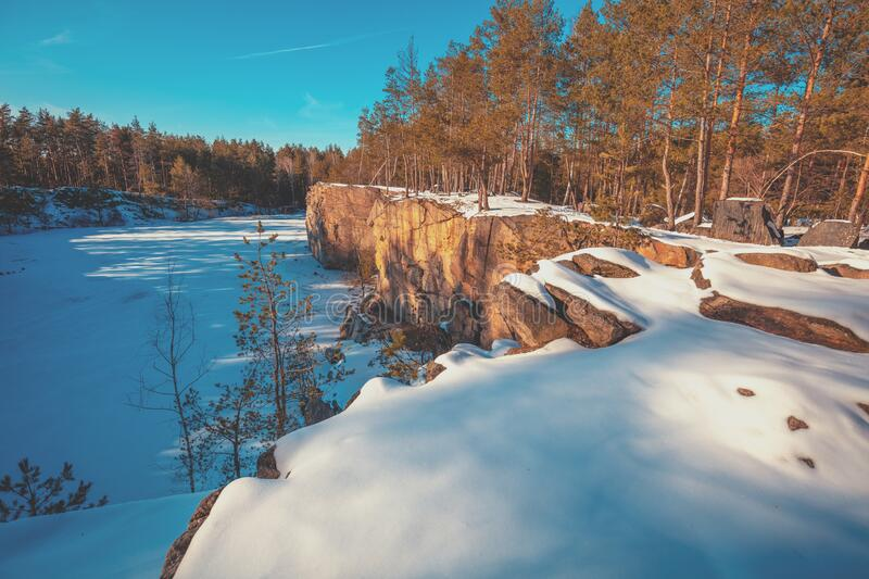 Granite rocky frozen lake shore. Winter nature. Granite rocky frozen lake shore. Granite quarry on a sunny day royalty free stock photography