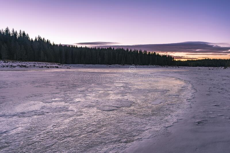 Winter nature. Snowy icy lake shore in mountains. Scenic winter landscape. Beautiful ice mountain lake.  stock image