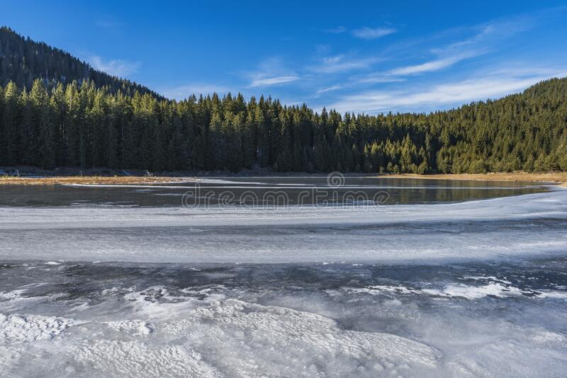 Winter nature. Snowy icy lake shore in mountains. Scenic winter landscape. Beautiful ice mountain lake. Winter nature. Snowy icy lake shore in mountains. Scenic royalty free stock image