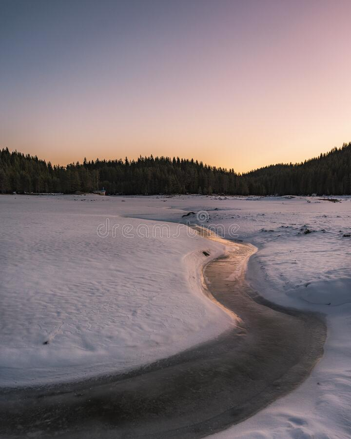 Winter nature. Snowy icy lake shore in mountains. Scenic winter landscape. Beautiful ice mountain lake.  stock photos
