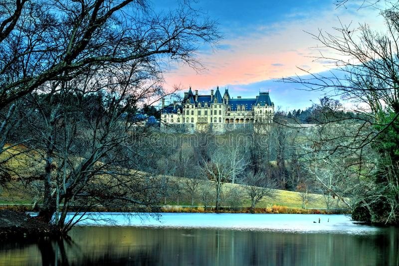 Winter Night At The Biltmore Lagoon. Winter is here if not officially. While waiting for the sun to set and the house to illuminate with lights the setting sun royalty free stock photos