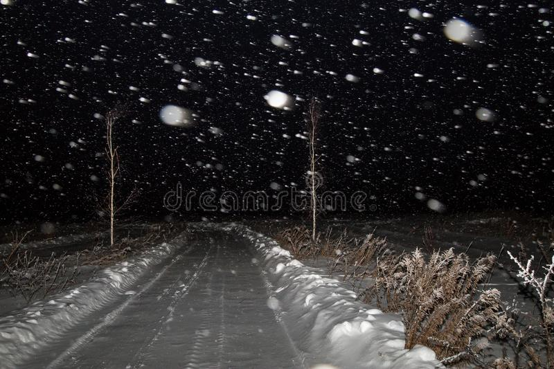 Winter night landscape with road in a field in the snow. The snowfall, blizzard and the dark sky stock photos