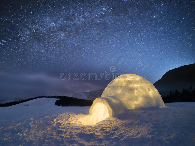 Winter night landscape with a snow igloo and a starry sky royalty free stock image