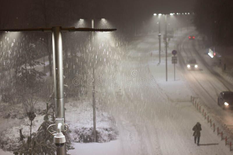 Winter night landscape, snowfall, a man walking along the road stock photography