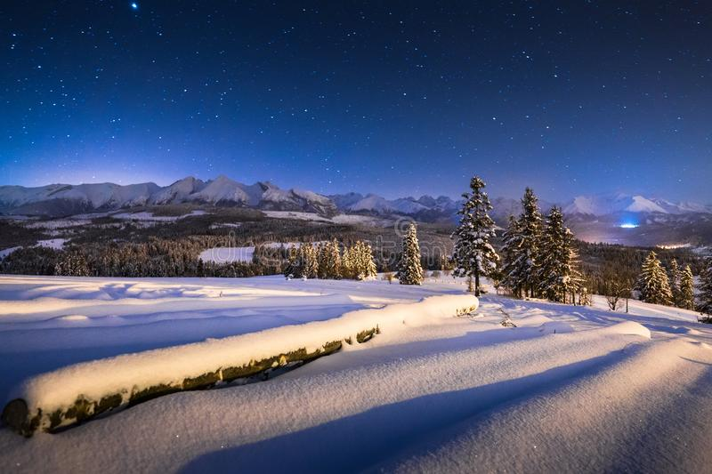 Winter night landscape. Starry blue night sky over winter mountains. Christmas night scenery in mountains royalty free stock photos
