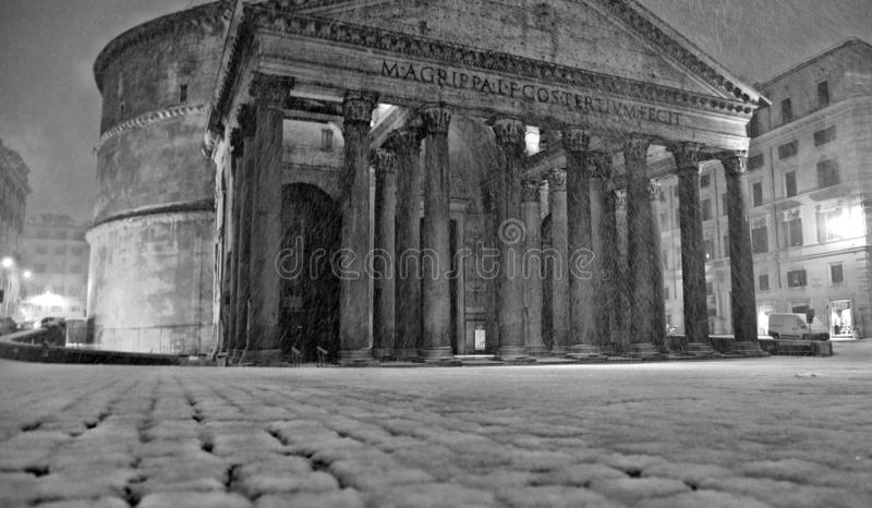 Winter night in Rome with snow blizzard and Pantheon temple church in empty square with golden light , Italy royalty free stock photo