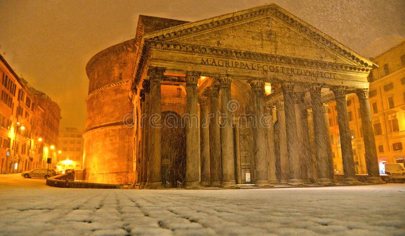 Winter night in Rome with snow blizzard and Pantheon temple church in empty square with golden light , Italy royalty free stock images
