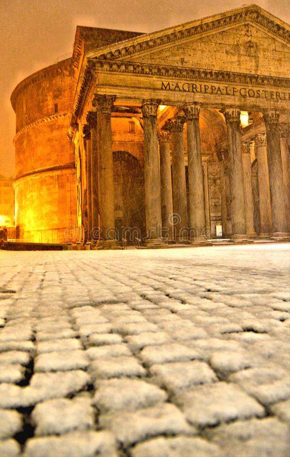 Winter night in Rome with snow blizzard and Pantheon temple church in empty square with golden light , Italy stock photos