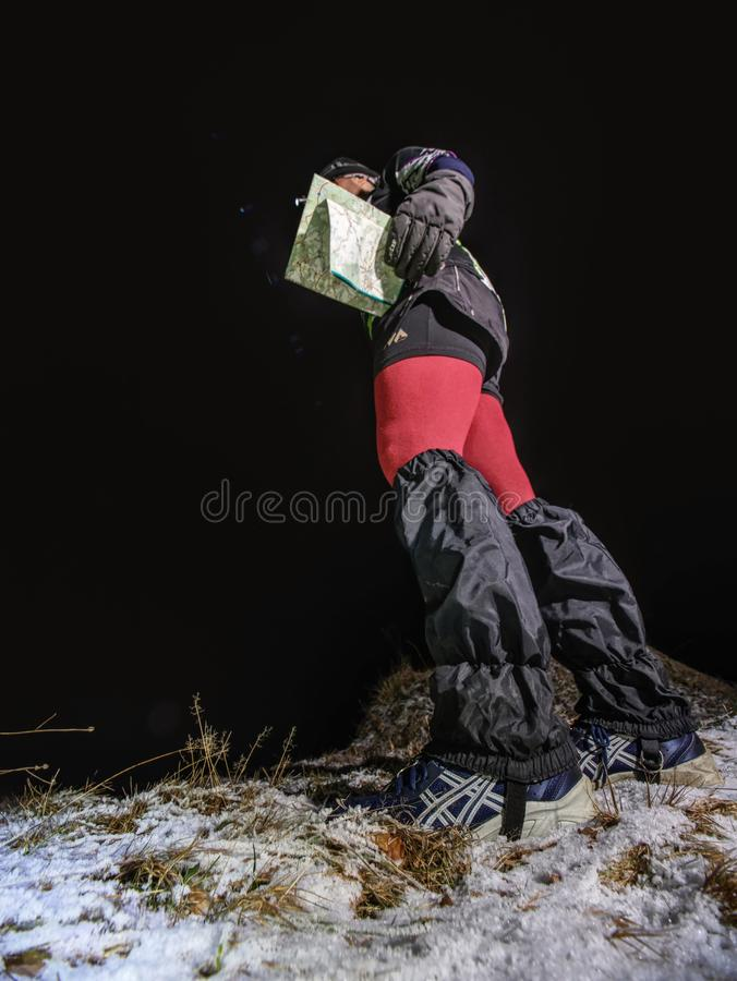 Winter night runner control possition. Girl in forest reading map stock photography
