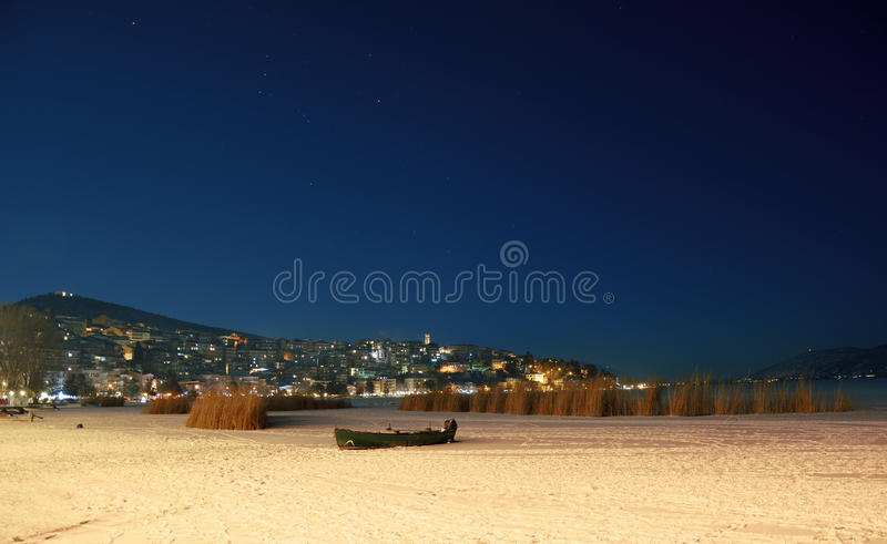Winter night scenery in town with frozen lake royalty free stock photo