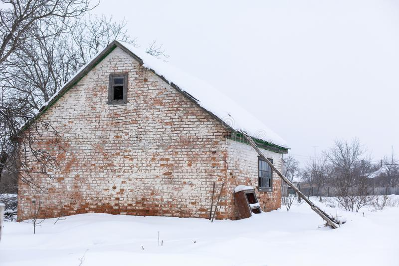 Winter, old dilapidated barn. A lot of snow around.  royalty free stock photo