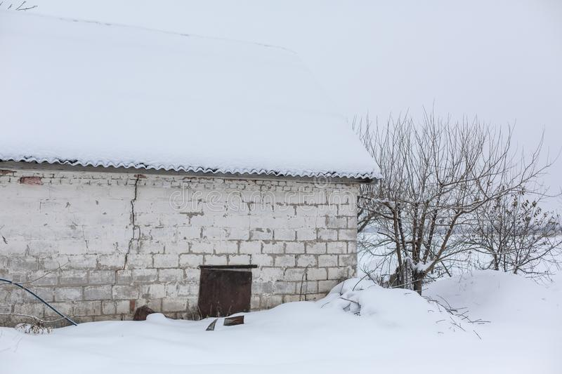 Winter, old dilapidated barn. A lot of snow around.  stock photos