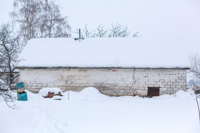 Winter, old dilapidated barn. A lot of snow around.  royalty free stock image