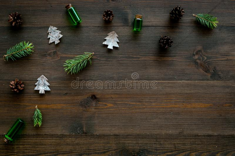 Winter ornament, New Year pattern. Pine sprigs, cones, spruce figure, fir oil on dark wooden background top view copy stock photography