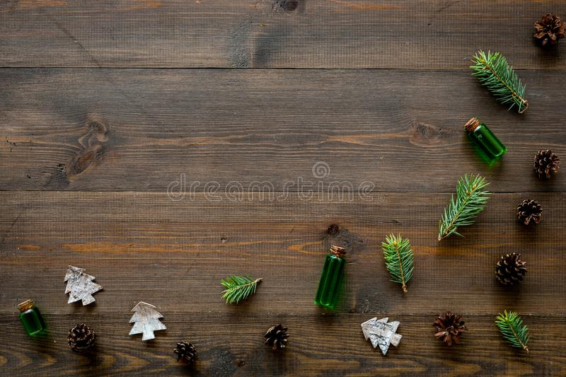 Winter ornament, New Year pattern. Pine sprigs, cones, spruce figure, fir oil on dark wooden background top view copy stock image