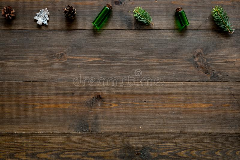 Winter ornament, New Year pattern. Pine sprigs, cones, spruce figure, fir oil on dark wooden background top view copy stock images