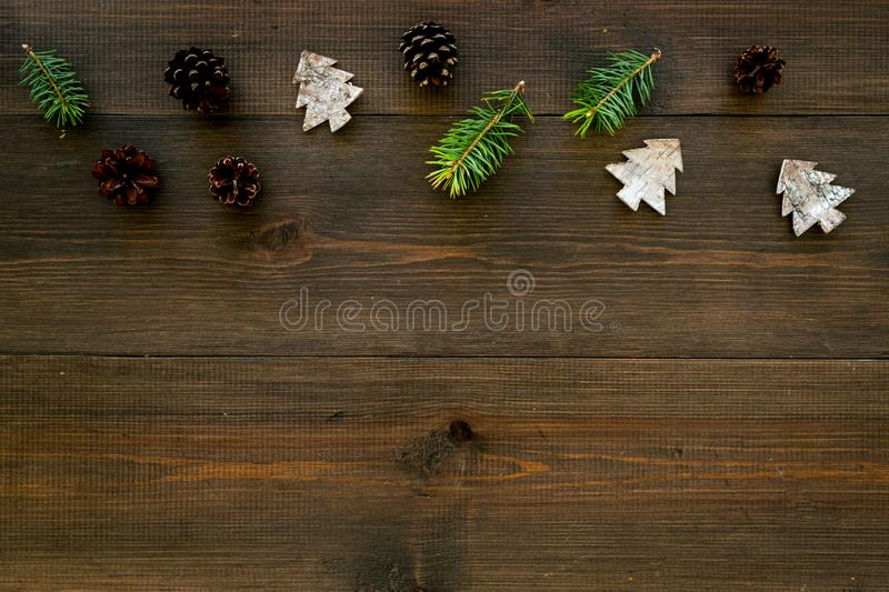 Winter ornament, New Year pattern. Pine sprigs, cones, spruce figure, fir oil on dark wooden background top view space stock image