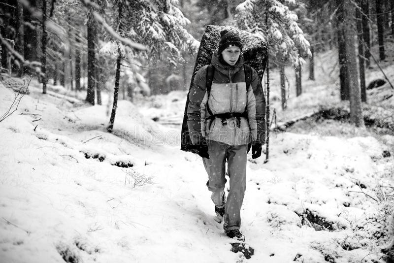 Winter outdoor leisure. Professional rock climber with a crash pad on his back in a snowy forest,Extreem sport. Karelia, Russia. stock image