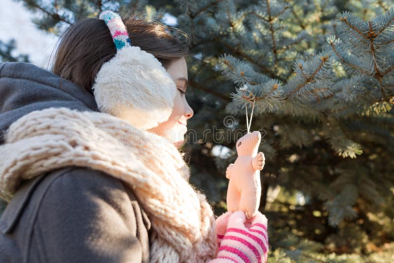 Winter outdoor portrait of child girl near the Christmas tree stock photo