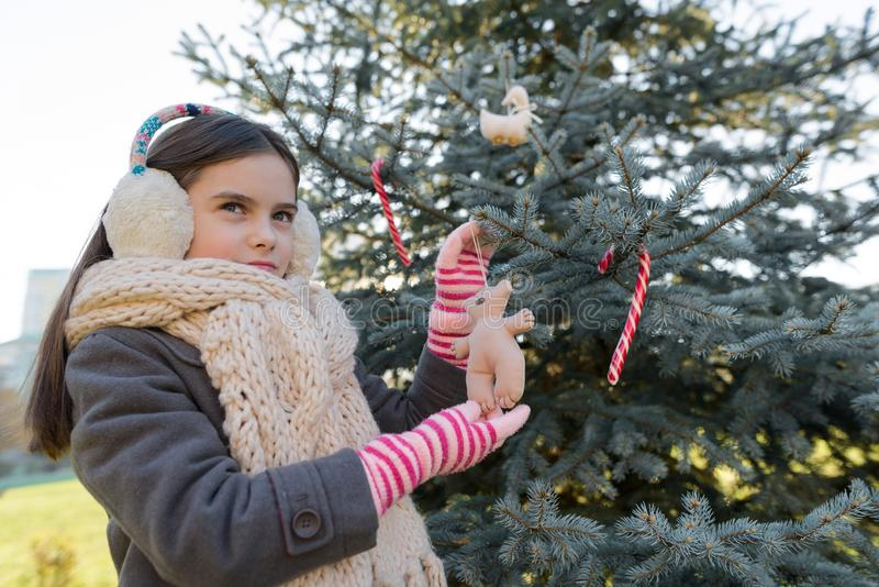 Winter outdoor portrait of child girl near the Christmas tree stock images