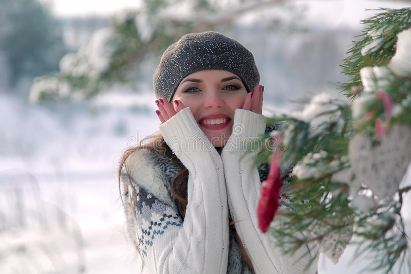 Winter outdoor portrait of a cute cheerful positive young girl with red heart decoration on a natural background royalty free stock photo