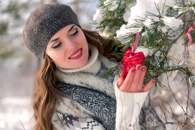 Winter outdoor portrait of a cute cheerful positive young girl with red heart decoration on a natural background stock photos