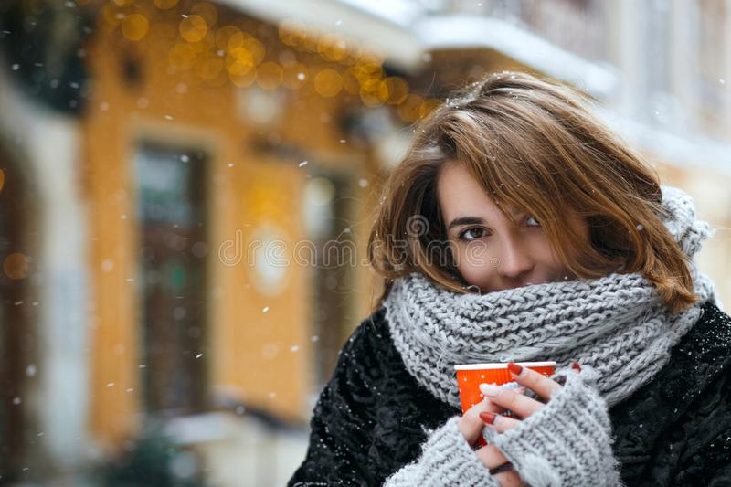 Winter outdoor portrait of tender brunette woman drinking coffee at the street. Empty space royalty free stock photo