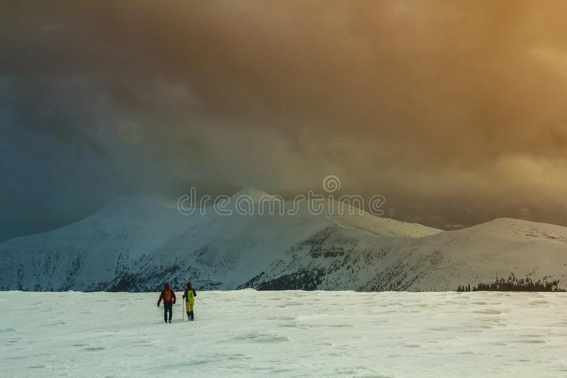 Winter panorama. Back view of two tourists hikers with backpacks. Going in snowy valley to magnificent mountain range under gloomy cloudy sky. Active lifestyle royalty free stock images