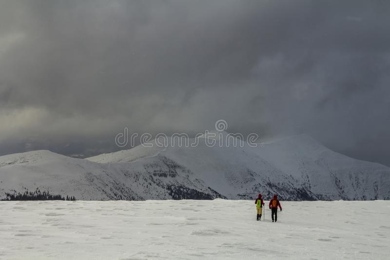 Winter panorama. Back view of two tourists hikers with backpacks going in snowy valley to magnificent mountain range under gloomy. Cloudy sky. Active lifestyle royalty free stock images