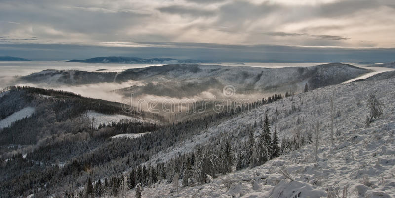 Winter panorama of Beskids mountains with only highest hills above misty level. From Beskid Slaski main ridge above Wisla stock image