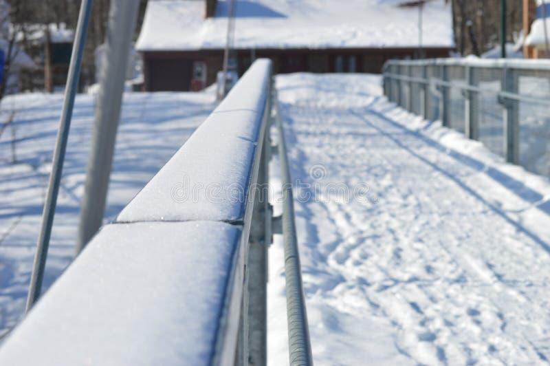 Winter pedestrian bridge and grilling. Winter in Canada, snow in Quebec. Winterland landscape. Iron bridge on a frozen river. Pedestrian trestle and bridge stock image