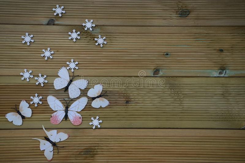 Winter photography image of white winter snowflakes and fun toy butterflies on rustic wood background and space stock photo