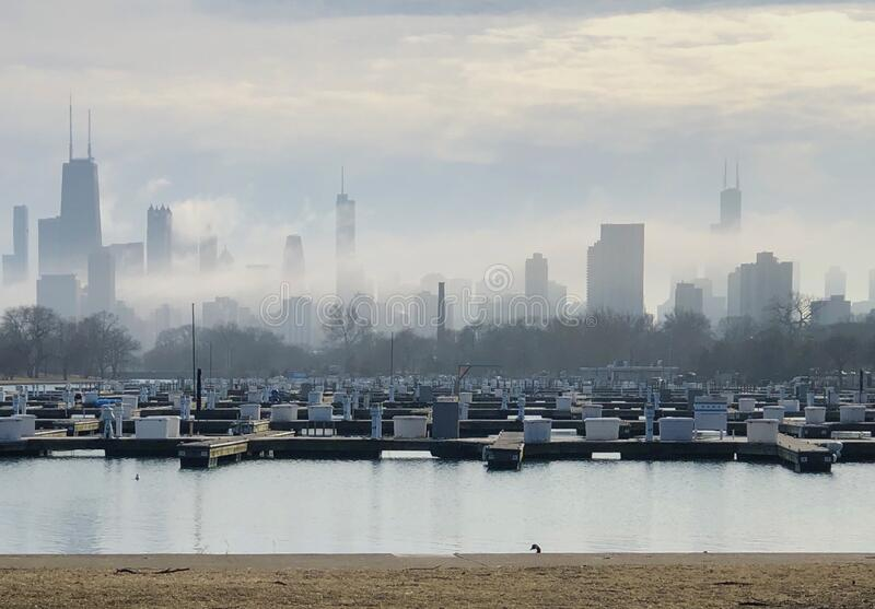 Skyline in Ground Fog #2. This is a winter picture of ground fog moving through the Chicago skyline from Diversey Harbor located in a Chicago, Illinois in Cook stock photography