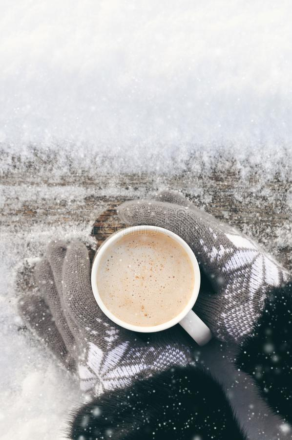Winter picture: hands in knitted gray gloves holding a Cup of hot coffee on a snowy day on a wooden rustic background in the stock photo