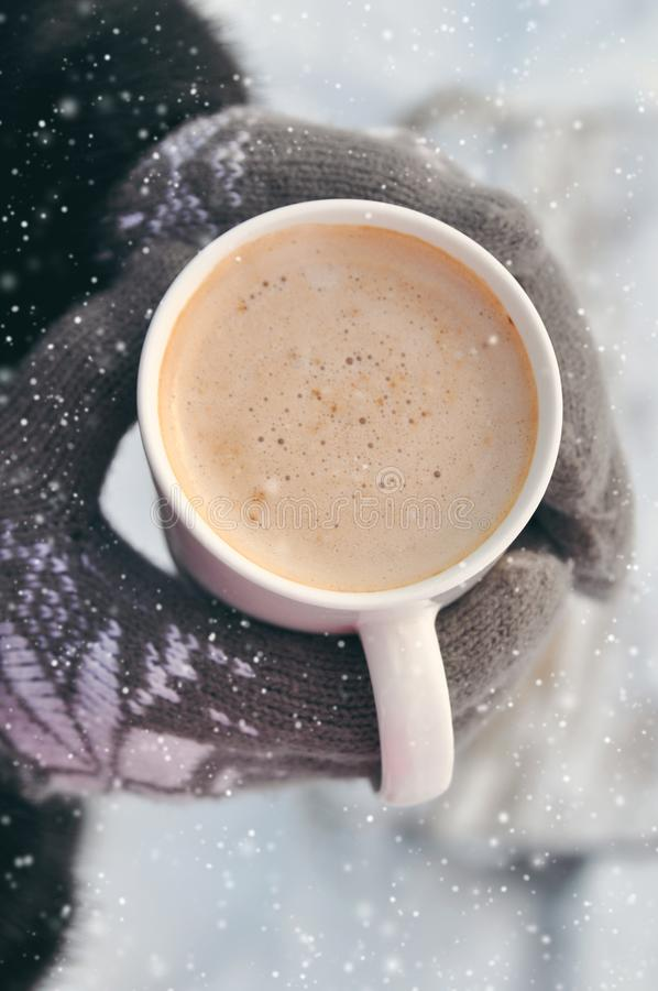 Winter picture: hands in knitted gray gloves holding a Cup of hot coffee on a snowy day on a wooden rustic background in the stock photos