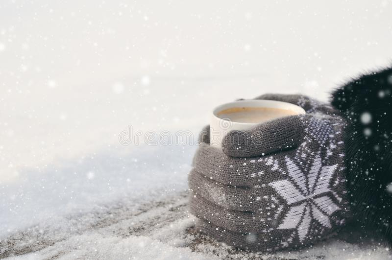 Winter picture: hands in knitted gray gloves holding a Cup of hot coffee on a snowy day on a wooden rustic background in the stock images