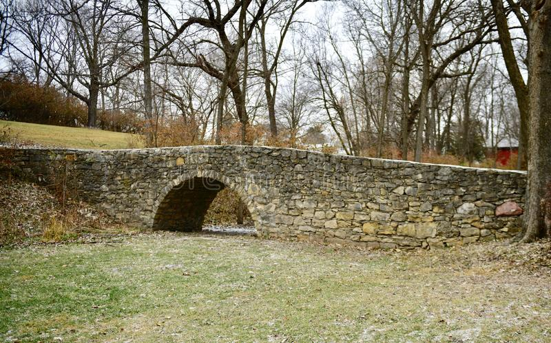 Stone Bridge Side View. This is a Winter picture of the side view of the iconic Stone Bridge over a small creek in Winterset Park located in Winterset, Iowa in stock photography