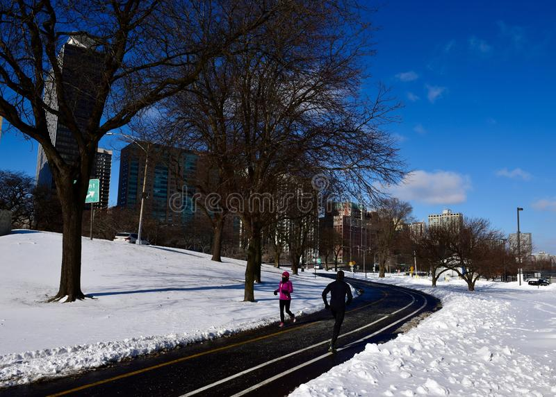 Chicago Lakefront Trail. This is a Winter picture of two joggers on the freshly snow cleared Chicago Lakefront Trail along Lake Michigan in Lincoln Park royalty free stock photography