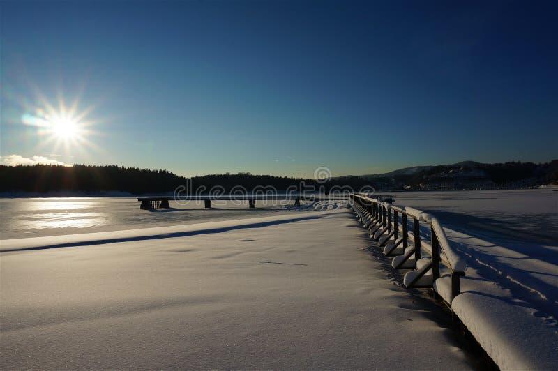 Winter pier frozen water at sunrise stock image
