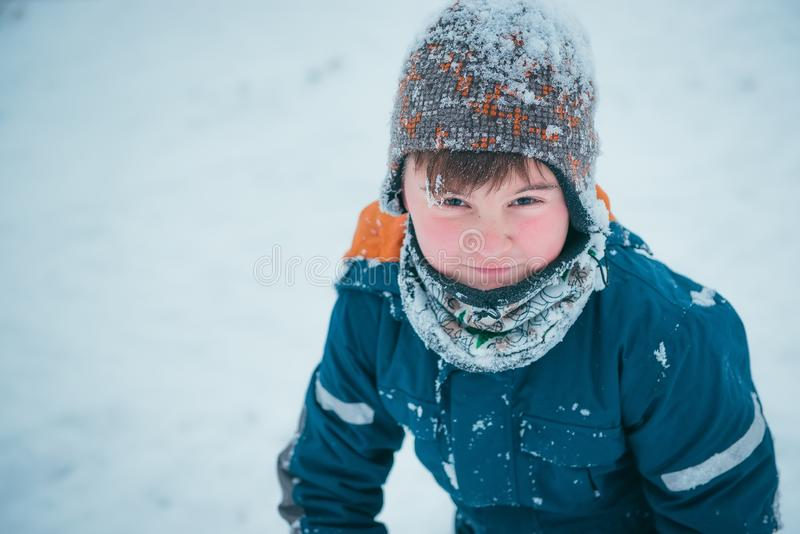 Winter portrait of boy, outdoors during snowfall. Active outdoor stock photography