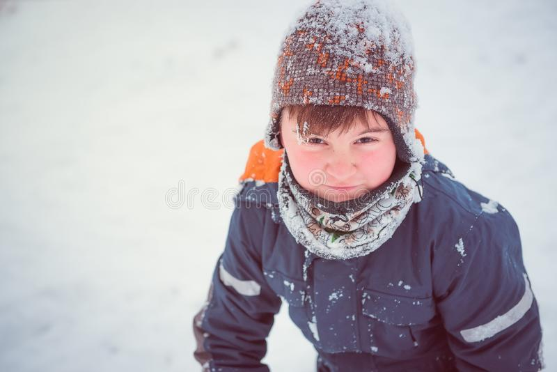 Winter portrait of boy, outdoors during snowfall. Active outdoor royalty free stock image