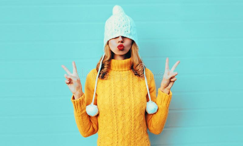 Winter portrait cool young woman having fun pulls a hat over her eyes wearing yellow knitted sweater and white hat with pom pom. Female blowing red lips making royalty free stock photos
