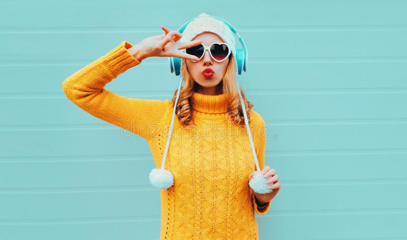 Winter portrait cool young woman in wireless headphones listening to music blowing red lips wearing yellow knitted sweater stock photo