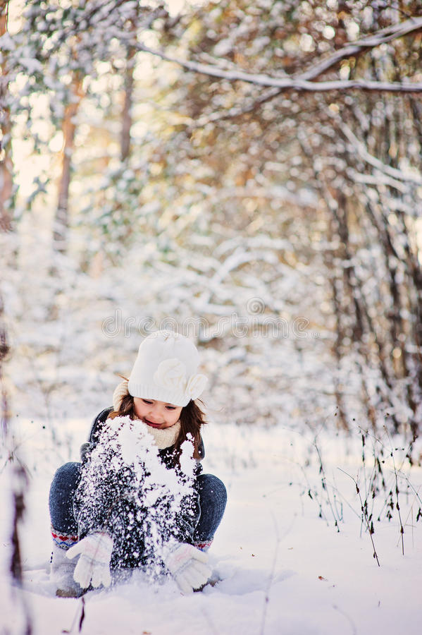 Winter portrait of cute happy child girl in grey fur coat plays with snow in forest. Winter portrait of cute happy child girl in grey fur coat plays with snow in royalty free stock photos