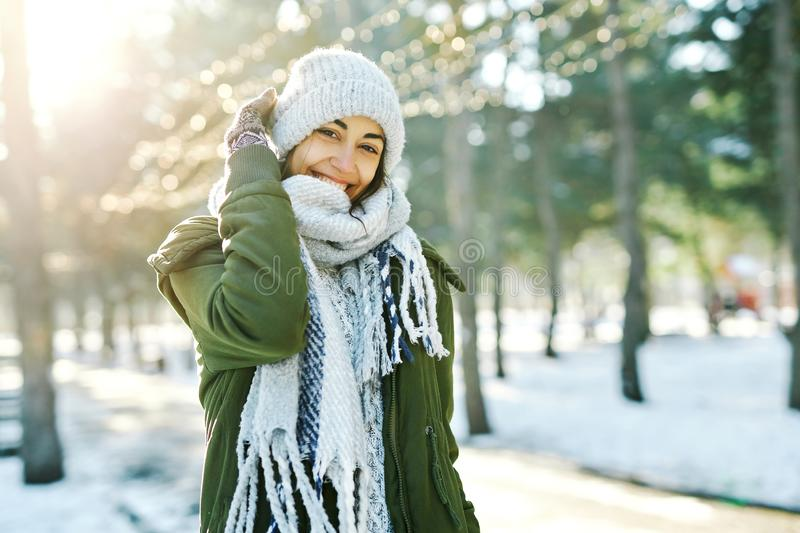 Winter portrait of funny smiling woman in woolen hat and long warm scarf in snowy winter park stock images