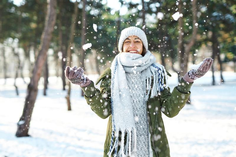 Winter portrait of funny woman in woolen hat and long warm scarf throwing snow in winter park, flying snowflakes. stock photos