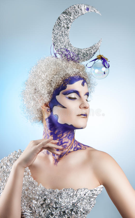 Winter portrait of a girl with creative make-up on a light background. Purple - Gold Makeup. Lunar silver in the hair of curls. Woman with eyes closed stock images